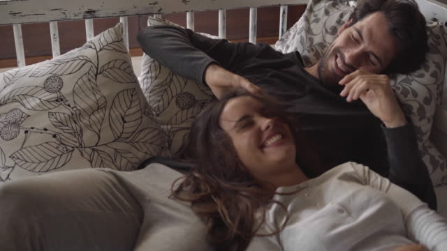 stockvideo's en b-roll-footage met dolly shot of man playing with woman's hair while lying on bed at home - driekwartlengte