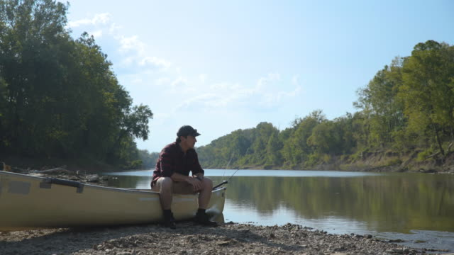 Dolly shot of man sitting on boat by lake against sky in forest