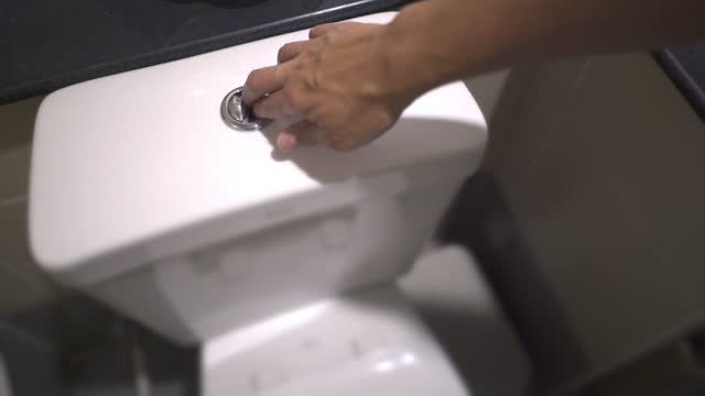 dolly shot of man's hand flushing water in toilet - tank stock videos & royalty-free footage