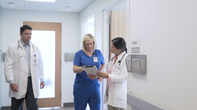 dolly shot of mature female doctors discussing over tablet computer while standing at corridor in hospital - scrubs stock-videos und b-roll-filmmaterial