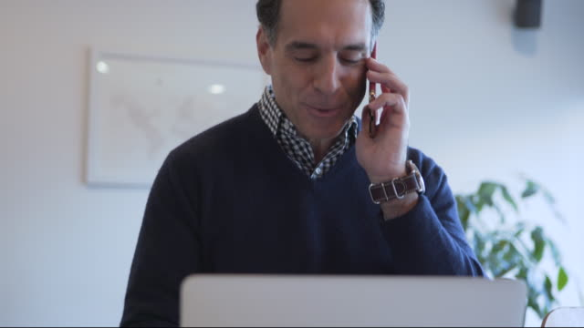 Dolly shot of mature man talking on smart phone while using laptop computer