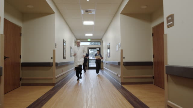 Dolly shot of medical staff running down a corridor