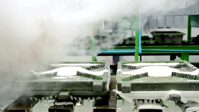 Dolly shot of metal latex pillow mold moving out of machine with heat steam on conveyor belt in latex pillow factory