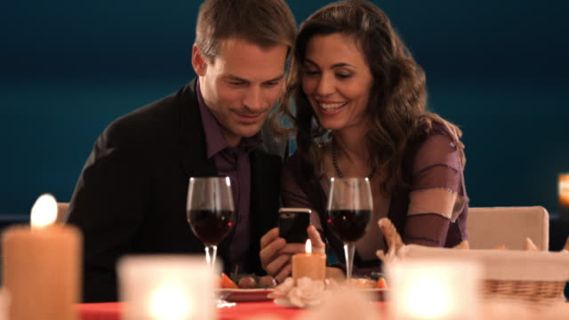 dolly shot of mid aged couple at dinner looking at phone - patio点の映像素材/bロール