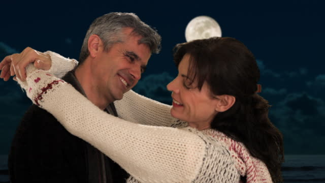 dolly shot of mid aged couple dancing in moonlight