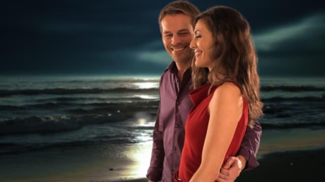 vídeos y material grabado en eventos de stock de dolly shot of mid aged couple walking on moonlit beach - novio relación humana