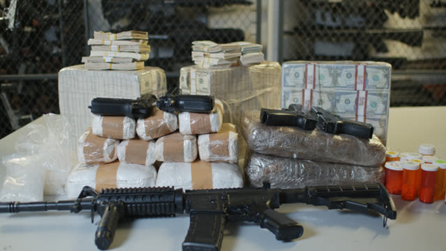 dolly shot of money, guns and drugs - arma da fuoco video stock e b–roll