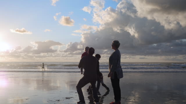 stockvideo's en b-roll-footage met dolly shot of mother looking man playing with son at beach - familie met drie kinderen