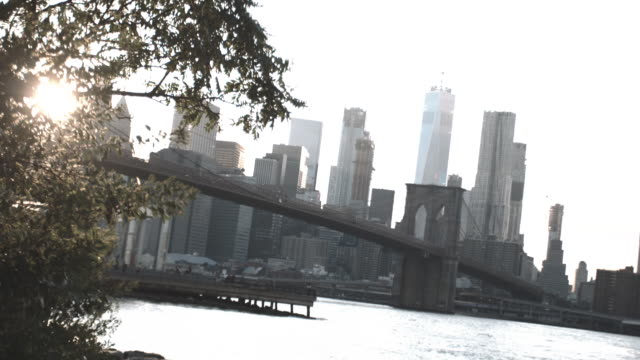 dolly shot of new york city's brooklyn bridge at sunset. - east river stock videos & royalty-free footage