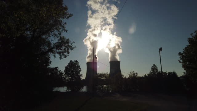 dolly shot of nuclear tower smoke and sunlight. - energy efficient stock videos & royalty-free footage