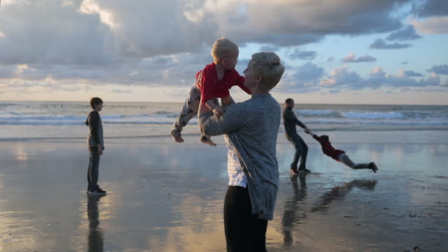 stockvideo's en b-roll-footage met dolly shot of parents playing with sons at beach against cloudy sky - familie met drie kinderen