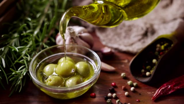 dolly shot of pouring olive oil on to olives in rustic kitchen - olive oil stock videos & royalty-free footage