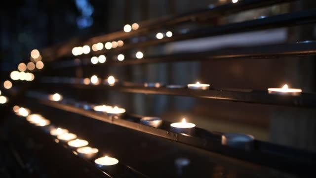 stockvideo's en b-roll-footage met dolly ontsproten van het bidden kaarsen in de kerk - panning