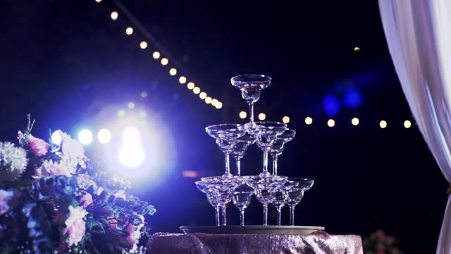 dolly shot of pyramid of empty champagne glasses in wedding ceremony with lighting outdoors at night. - expense stock videos and b-roll footage