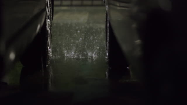 4k dolly shot of raindrop on the car at parking lot at night - parking stock videos & royalty-free footage