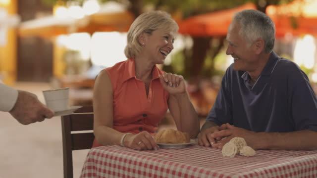vídeos y material grabado en eventos de stock de dolly shot of senior couple at cafe in town waiter bringing coffee - brazo humano