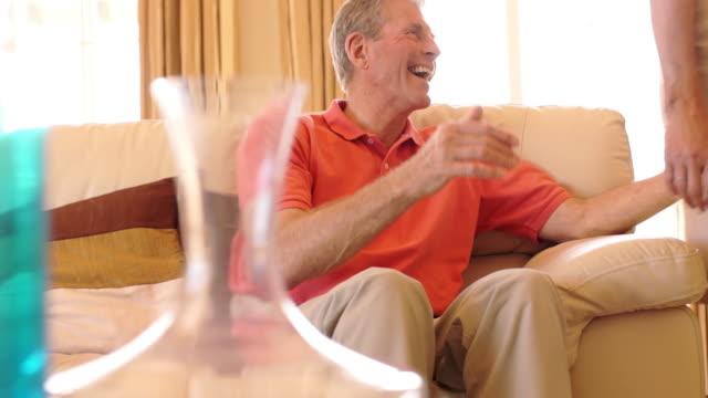 vídeos de stock e filmes b-roll de dolly shot of senior couple hugging on sofa together. - fotografia de três quartos