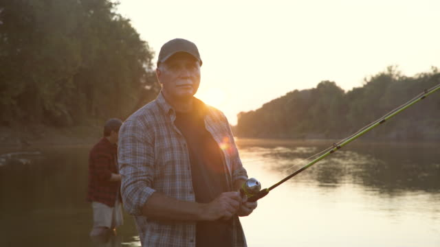 dolly shot of senior man holding fishing rod standing with son in lake against sky during sunset - fishing rod stock videos & royalty-free footage