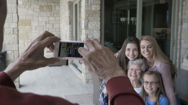 vídeos y material grabado en eventos de stock de dolly shot of senior man photographing family through smart phone on porch - sms
