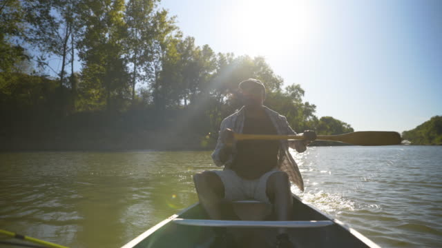 dolly shot of senior man rowing boat on lake against clear sky at forest during sunny day - oar stock videos & royalty-free footage