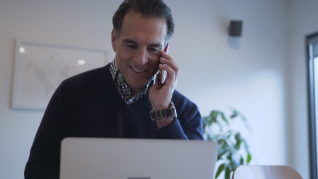 Dolly shot of smiling mature man talking on smart phone while using laptop computer
