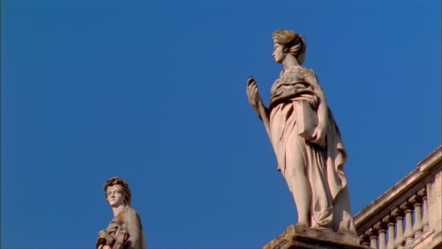 Dolly shot of statues of Roman goddesses standing on top of Grand Theatre de Bordeaux on clear day / Bordeaux, France