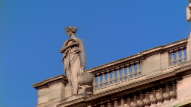 dolly shot of statues of roman goddesses standing on top of grand theatre de bordeaux on clear day / bordeaux, france - mythologie stock-videos und b-roll-filmmaterial