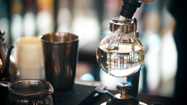 dolly schuss von syphon kaffee auf gasherd. - ausgusstülle stock-videos und b-roll-filmmaterial