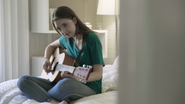 dolly shot of teenage girl playing guitar while sitting on bed in bedroom - griffbrett stock-videos und b-roll-filmmaterial