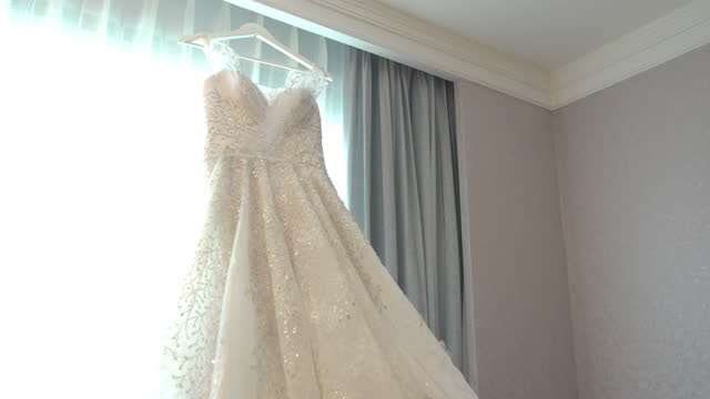 dolly shot of the wedding dress hangs in the window at the wedding day - dress stock videos & royalty-free footage