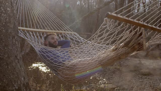 dolly shot of thoughtful man relaxing on hammock in forest - facial hair stock videos & royalty-free footage