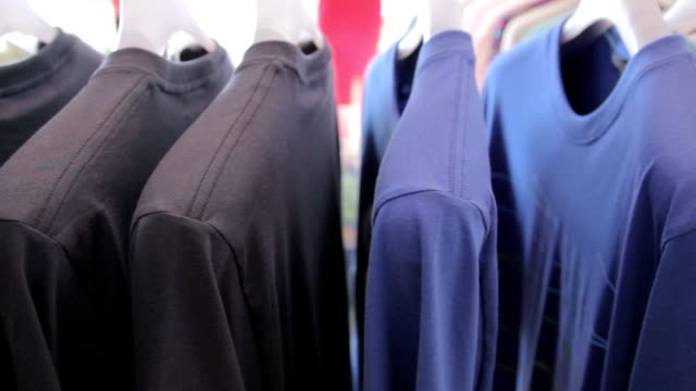 dolly shot of t-shirts on a coat rack - t shirt stock videos & royalty-free footage