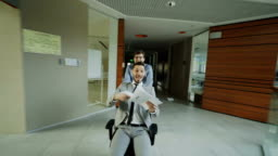 Dolly shot of Two crazy businessmen riding office chair and throwing papers up while having fun in lobby of modern business center