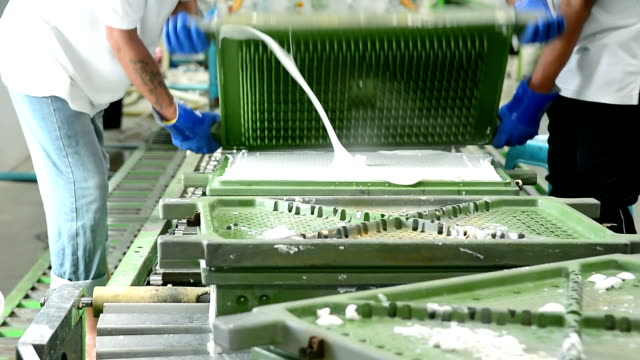 Dolly shot of two worker lift up metal mold of latex pillow on conveyor belt in latex pillow factory