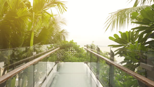 dolly shot of walking to the clear glass balcony that extends to take the sea view in pattaya, thailand. - building terrace stock videos & royalty-free footage
