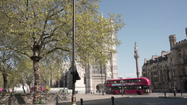 a dolly shot of westminster abbey revealed from behind a tree in glorious spring sunshine - westminster abbey stock videos & royalty-free footage