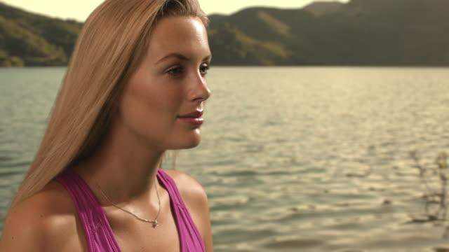 dolly shot of woman beside lake/marbella region, spain - 若い女性だけ点の映像素材/bロール