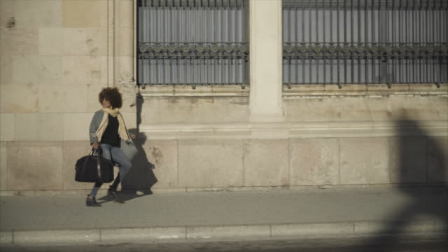 dolly shot of woman carrying bag while running on sidewalk by building in city - wide shot stock videos & royalty-free footage