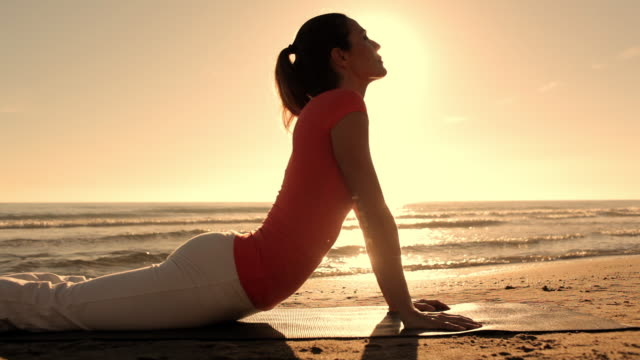 Dolly shot of woman doing yoga on beach/Marbella region, Spain