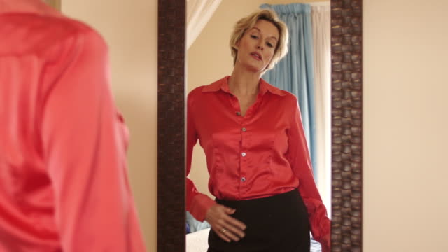Dolly shot of woman in bedroom getting dressed in mirror.