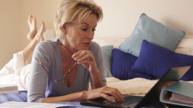 vídeos y material grabado en eventos de stock de dolly shot of woman in bedroom lying on bed and working on computer. - 50 54 años