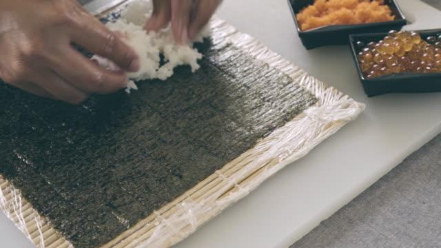 dolly shot of woman preparing rice on sushi. - salmon salad stock videos & royalty-free footage