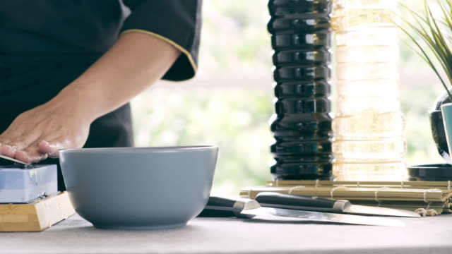 dolly schuss von frau setzen wasser auf stein und schärfen küchenmesser. - küchenmesser stock-videos und b-roll-filmmaterial