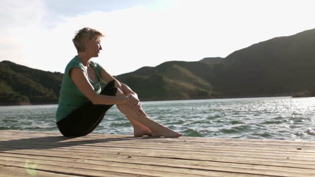 dolly shot of woman sitting and relaxing on jetty at lakeside. - jetty stock videos & royalty-free footage