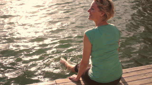 vidéos et rushes de dolly shot of woman sitting and relaxing on jetty at lakeside with feet in water. - cadrage aux genoux