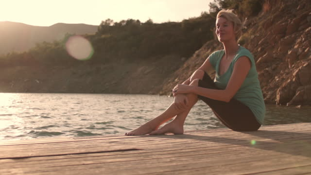 dolly shot of woman sitting on jetty by lakeside relaxing. - jetty stock videos & royalty-free footage