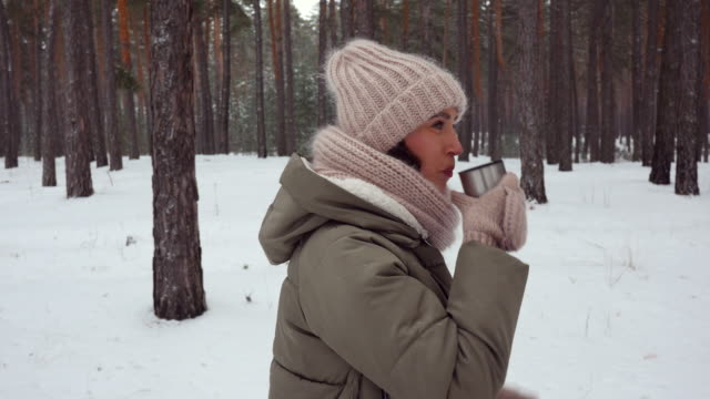 dolly shot of woman strolling in the forest on winter with a cup of hot tea - mitten stock videos and b-roll footage