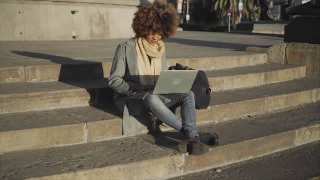 dolly shot of woman using laptop computer while sitting on steps outdoors - frizzy hair stock videos and b-roll footage