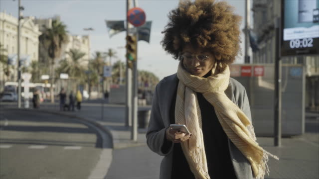 dolly shot of woman using smart phone while standing on footpath in city - frizzy hair stock videos and b-roll footage