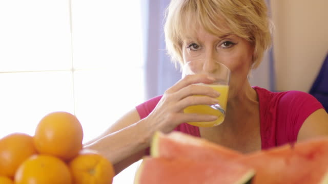 dolly shot of woman with fruit in foreground drinking glass of orange juice. - saft stock-videos und b-roll-filmmaterial